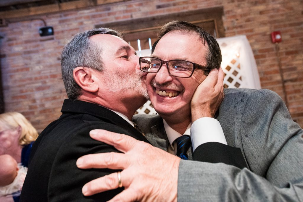 Man kissing another man on cheek joyously