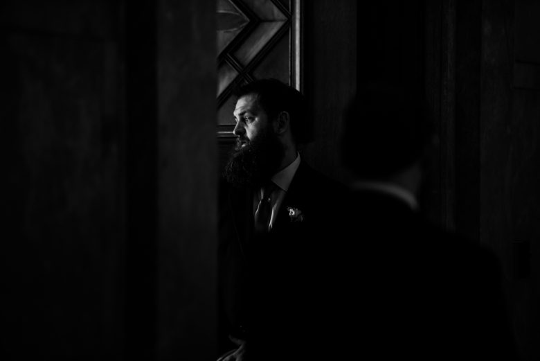 wedding photo black and white of bearded man illuminated by a narrow door.