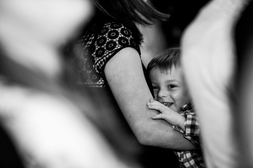 child in black and white smiles from his mothers arms who is out of frame